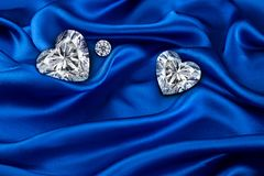 Free Diamonds On Blue Luxurious Cloth Silk, Wavy Fabric Satin And Gemstone Stock Photography - 104168452