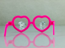 Diamonds and pink glasses. Pink glasses in the shape of hearts and diamonds visible in the distance. Calculating love Stock Image
