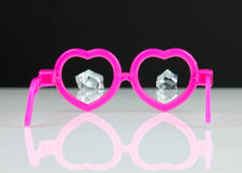 Diamonds and pink glasses. Pink glasses in the shape of hearts and diamonds visible in the distance. Calculating love Royalty Free Stock Images