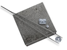 Diamonds and tweezers on a jeweler anvil Stock Photo