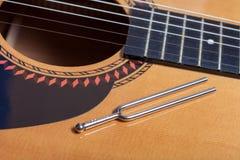 Diapason de musique sur des ficelles de guitare acoustique images stock