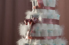 Diaper cake. Pink diaper cake with feathers Royalty Free Stock Photos