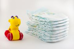 Diapers and a children`s toy on a white background infant stock photo