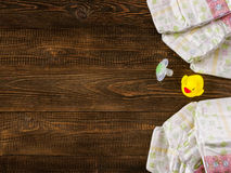 Diapers and dummy and rubber duckling on wooden background Stock Photos