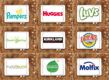 Diapers manufacturers logos and brands. Collection of most famous diapers companies on white tablet on wooden background. brands like pampers, huggies, luvs Stock Photography