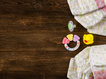 Diapers, teether, dummy and rubber duckling on wooden background Royalty Free Stock Images