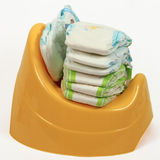 Diapers vs potty. Stack of diapers and yellow potty stock photos
