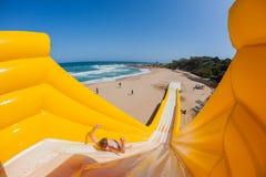 Diapositiva de apogeo de la atracción emocionante del muchacho de la playa Fotos de archivo