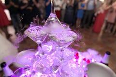 Diapositiva de Champán Pirámide o fuente hecha de los vidrios del champán con la cereza y el vapor del hielo seco Fotos de archivo libres de regalías