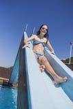 Diapositiva de la piscina de la muchacha feliz Fotografía de archivo libre de regalías