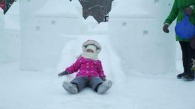Diapositiva del hielo de la niña que monta en la ciudad del hielo metrajes