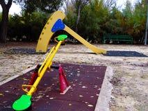 Diapositiva y eje de balancín amarillos en parque público fotos de archivo