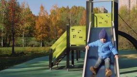 Diapositivas lindas del niño pequeño en diapositiva del patio almacen de metraje de vídeo