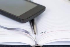 Diario abierto con la pluma y el smartphone Fotografía de archivo