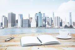 Diario abierto del espacio en blanco con la taza de café y de lentes en etiqueta de madera Fotos de archivo libres de regalías