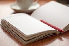 Diario abierto para escribir y bolígrafo en la tabla imagenes de archivo