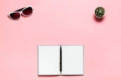 Diario in bianco aperto, penna nera, vetri bianchi sul fondo rosa del textplace Disposizione piana, vista superiore Area di lavor Fotografia Stock Libera da Diritti