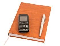 Diario cerrado con una pluma y un teléfono móvil imagenes de archivo