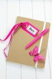 Diario con las decoraciones rosadas en superficie de madera Fotos de archivo