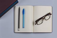 Diario con una pluma y un lápiz y vidrios foto de archivo