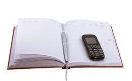 Diario con una pluma y un teléfono móvil imagenes de archivo