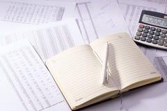 Diario con una pluma y una calculadora fotografía de archivo