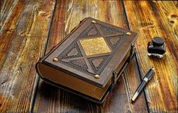 Diario de cuero con el adorno dorado y la pluma con la botella de tinta en el lado El libro se captura del lado derecho fotos de archivo