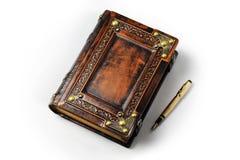 Diario de cuero grande con la pluma del oro en la sombra del libro imagenes de archivo