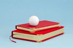 Diario di affari e sfera di golf dorati Immagini Stock Libere da Diritti