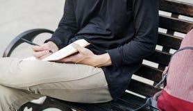 Diario di scrittura dell'uomo dello studente che raffredda sul banco Fotografie Stock