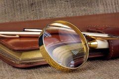 Diario dorato di affari della penna, lente d'ingrandimento sul licenziamento Fotografia Stock