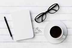 Diario en blanco, pluma, taza de café, clips y vidrios en la madera blanca Fotos de archivo