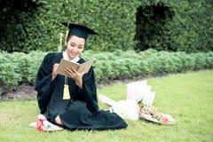Diario graduado de la lectura, cuaderno en su mano que siente relajante Foto de archivo libre de regalías