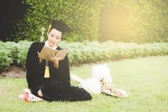 Diario graduado de la lectura, cuaderno en su mano que siente relajante y tan felicidad foto de archivo libre de regalías