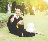 Diario graduado de la lectura, cuaderno en su mano que siente relajante y tan felicidad en día de comienzo foto de archivo
