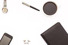Diario negro, pluma, taza de café sólo y teléfono en el fondo blanco Concepto mínimo del negocio para la mesa en la oficina Imagen de archivo libre de regalías