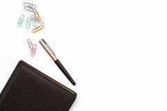 Diario negro, pluma y paperclips coloreados en el fondo blanco Escritorio en la oficina concepto mínimo del negocio Endecha plana Fotografía de archivo libre de regalías