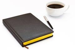 Diario nero nella priorità alta e una tazza di caffè dietro su un fondo bianco Immagine Stock Libera da Diritti