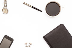 Diario nero, penna, tazza di caffè nero e telefono su fondo bianco Concetto minimo di affari per il desktop nell'ufficio Immagine Stock Libera da Diritti