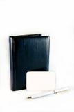 Diario oscuro de cuero y pluma blanca cerca de una tarjeta en blanco para escribir Fotografía de archivo libre de regalías