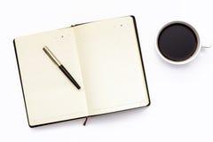 Diario, pluma y taza abiertos del negro de café sólo en un fondo blanco Concepto mínimo del negocio para el lugar de trabajo en l fotos de archivo libres de regalías