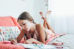 Diario pre teenager di scrittura della ragazza Fotografia Stock