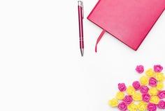 Diario rosado con una pluma y pequeñas rosas rosadas amarillas en un fondo blanco Imagenes de archivo