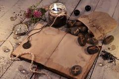 Diario viejo con las velas negras, las runas antiguas y el reloj en tablones de madera Imagenes de archivo