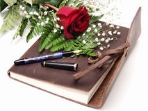 Diary 140. A leatherbound diary with a pen and red rose, on an isolated white background Stock Photo