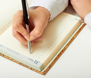 Diary. Woman's hand writing black pen in a notebook Royalty Free Stock Images