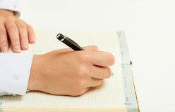 Diary. Woman's hand writing black pen in a notebook Stock Photography