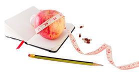 Diary with apple and pills for effective dieting. Diary with fruit and biologically active supplement in pills for efficient dieting Royalty Free Stock Photos