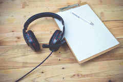 Diary. Blank diary and pen earphone on wood background Royalty Free Stock Image