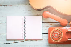 The diary blanks with retro telephone and acoustic guitar Royalty Free Stock Photos